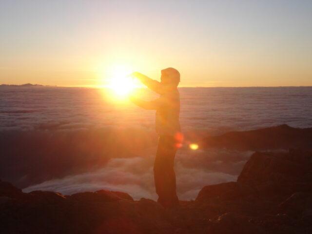 Miriam auf dem Vulkan Aconcagua beim Sonnenaufgang. Es sieht so aus als ob sie die Sonne in den Händen hält.