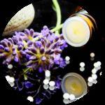 Lavendel, ein Fläschchen und homöopathische Kügelchen liegen auf einer Platte, die alles leicht widerspiegelt.