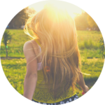 Eine Frau mit langen blonden Haaren rennt der Sonne entgegen.