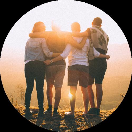 Vier Menschen stehen nebeneinander und halten sich im Arm. Sie schauen in den Sonnenaufgang und sind auf dem Bild nur von Hinten sichtbar