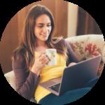 Frau sitzt auf Couch mit einem Tee in der Hand und einem Laptop auf den Beinen